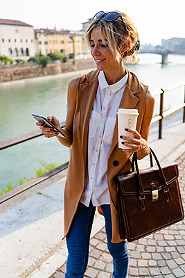 Smiling woman with coffee to go using smartphone in the city - p300m2139988 by Giorgio Fochesato