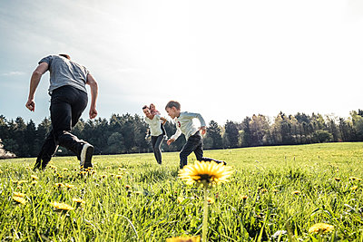 Family with two kids having fun together on a meadow in spring - p300m2167628 by Wilfried Feder