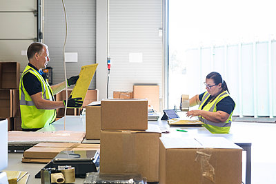 Coworkers packing merchandise on desk at distribution warehouse - p426m2018798 by Maskot