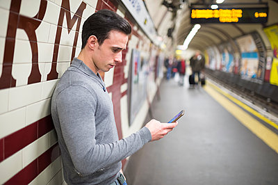Side view of man on railway platform looking at smartphone - p429m1197956 by Ben Pipe Photography