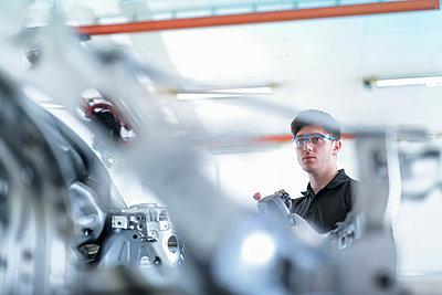 Apprentice engineer measuring car body in car factory - p429m1417794 by Monty Rakusen
