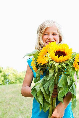 Smiling girl carrying sunflowers - p429m711675f by Emely