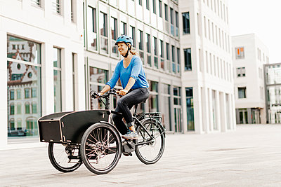 Young woman rides a cargo e-bike - p608m2192839 by Jens Nieth