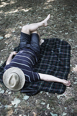 Man lying on a blanket in a park - p7030039 by Anna Stumpf