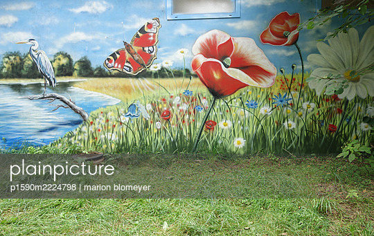 Lawn and mural depicting a blooming meadow - p1590m2224798 by marion blomeyer