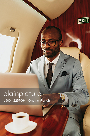 Young male entrepreneur working on laptop while traveling in private jet - p300m2257064 by OneInchPunch