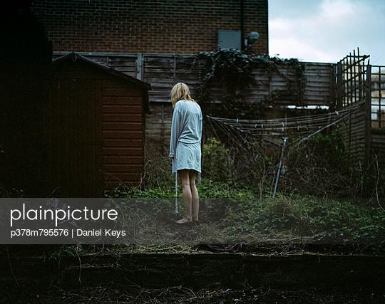 Girl in rundown garden - p378m795576 by Daniel Keys