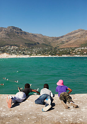 3 afrikanische Jungs liegen auf Promenade - p045m1362804 von Jasmin Sander