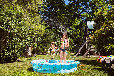 Girl playing with water while standing in wading pool at yard - p1166m1164548 by Cavan Images