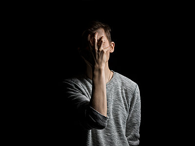 Man covering face with hand while standing against black background - p1166m2060696 by Cavan Social
