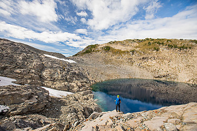 Backpacker stands above cirque lake in backcountry, B.C., Canada. - p1166m2095286 by Cavan Images
