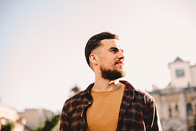 Portrait of confident young hipster man against clear sky in city - p1166m2153308 by Cavan Images