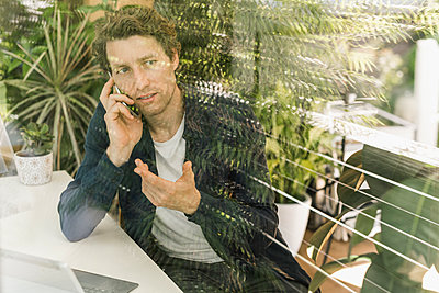 Man talking on smart phone while sitting at home - p300m2227194 by Uwe Umstätter
