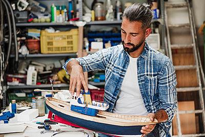 Male craftsperson building ship model at workshop - p300m2293387 by Eva Blanco