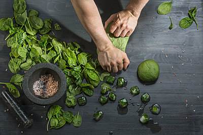 Cropped image of hands kneading green dough by basil ice cubes at table - p301m1180583 by Vladimir Godnik