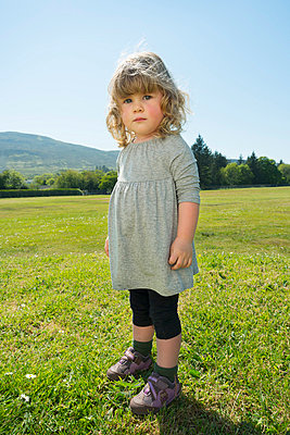 Girl standing in grassy field - p429m696582 by Mischa Keijser