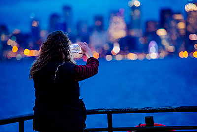 Caucasian woman on boat photographing urban waterfront with cell phone - p555m1232001 by Pete Saloutos