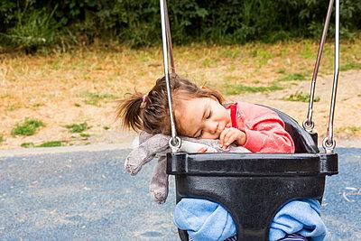 Caucasian baby girl sucking thumb in swing - p555m1303594 by Adam Hester