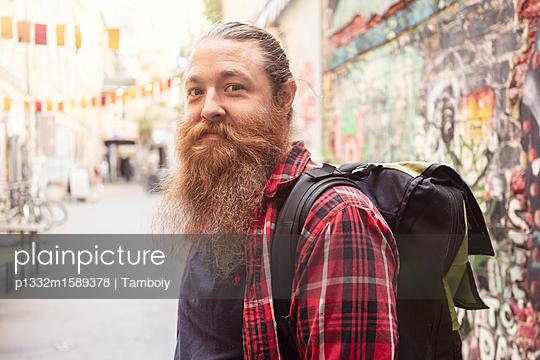 Porträt eines männlichen Hipster mit Rucksack - p1332m1589378 von Tamboly