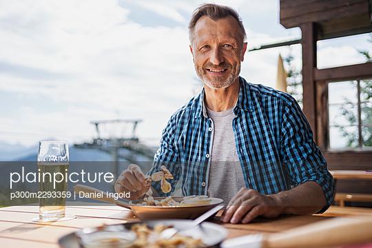 Smiling man having food at restaurant - p300m2293359 by Daniel Ingold