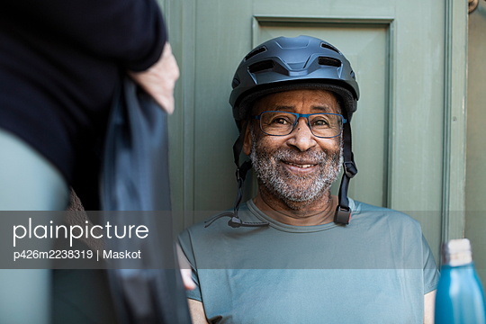 Smiling senior man with bottle against doorway - p426m2238319 by Maskot