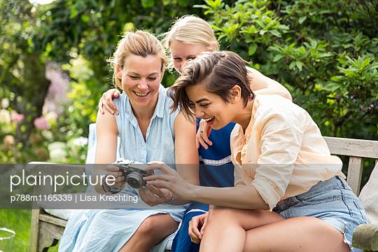 Drei Frauen auf der Gartenbank mit Fotoapparat - p788m1165339 von Lisa Krechting