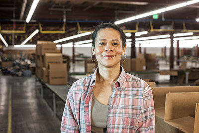 Portrait of an African American female warehouse worker in a large distribution warehouse with products stored in cardboard boxes. - p1100m1575468 by Mint Images