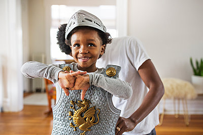Father assisting cheerful boy in getting dressed as armor at home - p1166m1140348 by Cavan Images