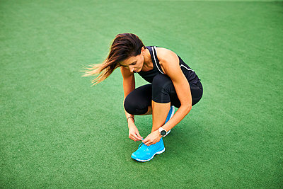 An athletic woman tying her sneakers. - p1166m2088740 by Cavan Images