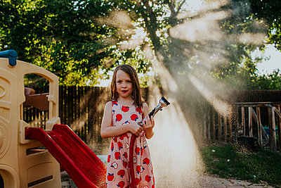 Young girl spraying mist from garden hose in backyard - p1166m2201609 by Cavan Images