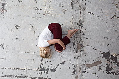 Woman lying in fetal position on the floor - p1301m1582536 by Delia Baum