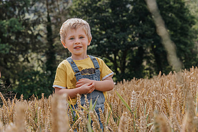 Smiling cute boy standing in barley field - p300m2275827 by Mareen Fischinger