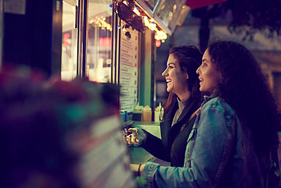 Smiling lesbian couple standing against concession stand in city at night - p426m2165350 by Maskot