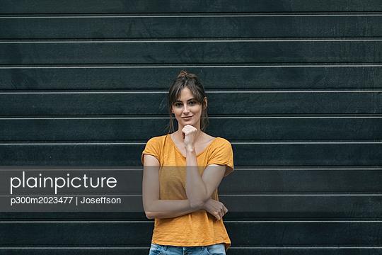 Portrait of a pretty woman in front of roller shutter - p300m2023477 von Joseffson