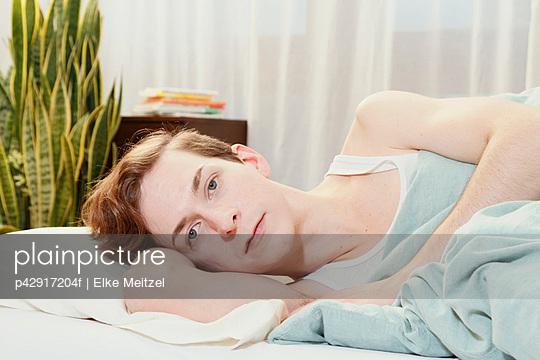 Man laying in bed - p42917204f by Elke Meitzel