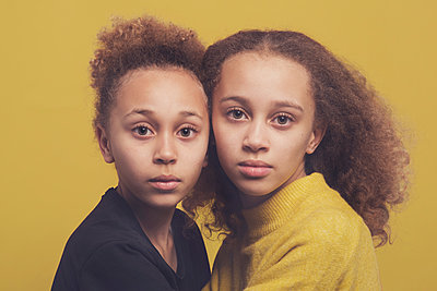 Studio portrait of two sisters with a yellow backdrop - p1323m2173835 von Sarah Toure