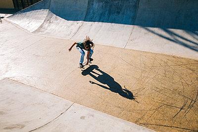 Young man with dreadlocks skateboarding in a skatepark - p300m1120442f by Kiko Jimenez