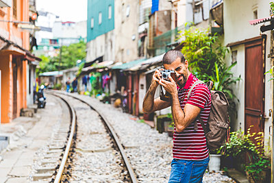 Vietnam, Hanoi, man in the city taking a picture with an old-fashioned camera - p300m1581371 by William Perugini