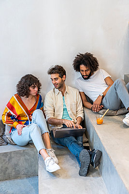 Three friends sitting on stairs with laptop and drink - p300m2113888 von VITTA GALLERY