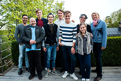 Portrait of happy multi-ethnic friends and family standing against hedge in yard - p426m1212745 by Maskot