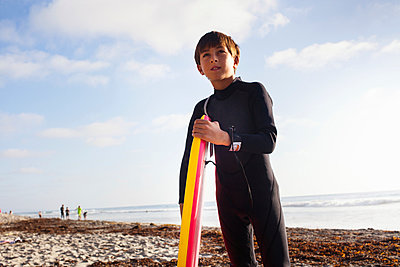 Young boy with surfboard on beach - p429m884153 by Yew! Images