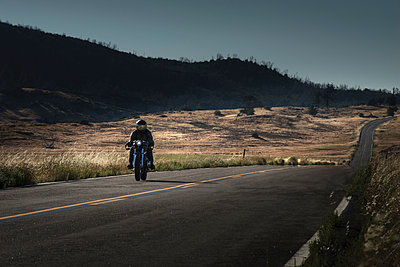 Mid adult male motorcyclist riding on highway - p429m974685 by JLPH