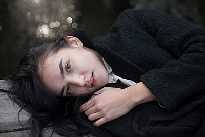 Portrait of serious Caucasian woman laying on wood - p555m1491515 by Dmitriy Bilous