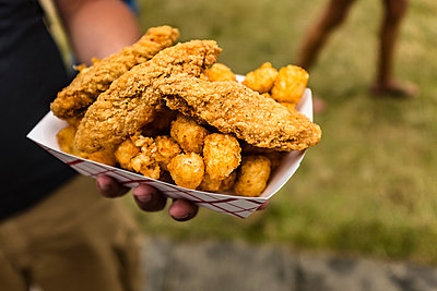 Hand holding container of fried chicken and potatoes - p555m1504049 by Steve Prezant