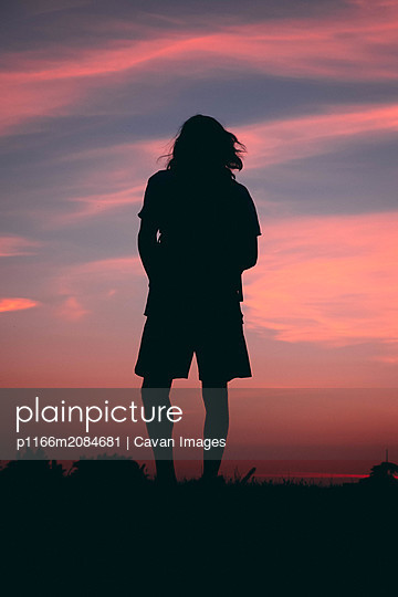Person at the top of hill watching the sunset - p1166m2084681 by Cavan Images