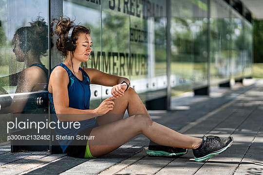 Young sportive woman wearing headphones and checking her smartwatch - p300m2132482 by Stefan Schurr