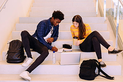 Friends discussing while sitting on steps at library - p1166m1530466 by Cavan Images