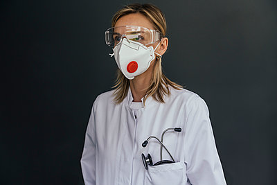 Portrait of doctor wearing FFP3 mask and safety glasses against grey background - p300m2198740 by Mareen Fischinger