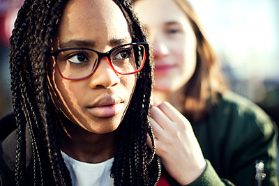 Thoughtful teenage girl wearing eyeglasses sitting with friend in city - p426m1179280 by Maskot
