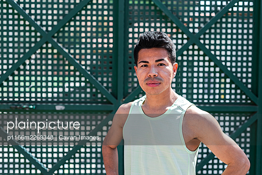 Portrait of a Latin American male athlete on green background. Running concept. - p1166m2269348 by Cavan Images
